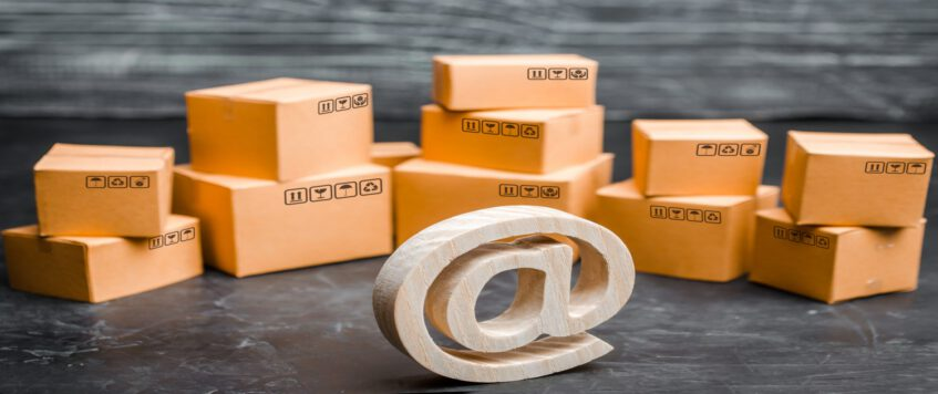Wooden email symbol on the background of a variety of boxes. Warehouse of goods, online store, sale of goods through the Internet. Online sales and e-commerce, product and brand promotion.